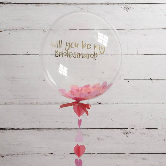 a cute personalized balloon filled with pink paper hearts and a thread of them