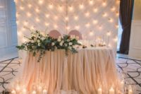20 a draped blush fabric backdrop with lots of lights perfectly matches the table decor and looks cute