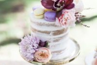 20 a naked wedding cake with blush blooms and a purple orchid plus colorful macaros on top