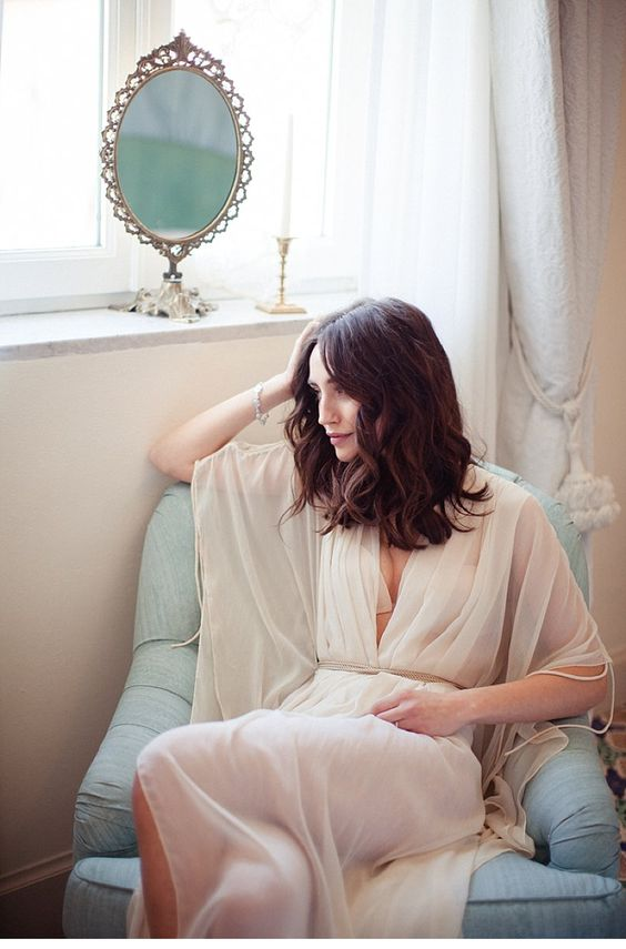 a simple off-white bridal robe with very wide sleeves and a draped bodice plus a woven sash