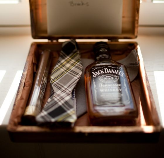 a small box with a cigar, a checked tie and Jack Daniel's for a simple and stylish proposal