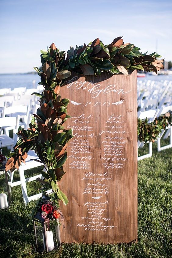 a wooden wedding program covered with a lush magnolia leaf garland