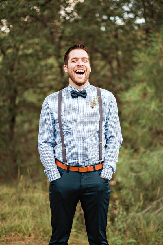 dark teal pants, a blue printed shirt, a black bow tie, brown suspenders and an amber leather belt ffor a stylish and simple look