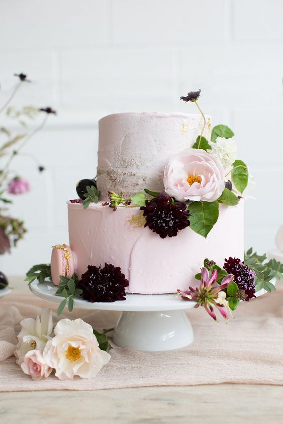 a blush wedding cake with blush macarons, a bloom and some deerp purple flowers