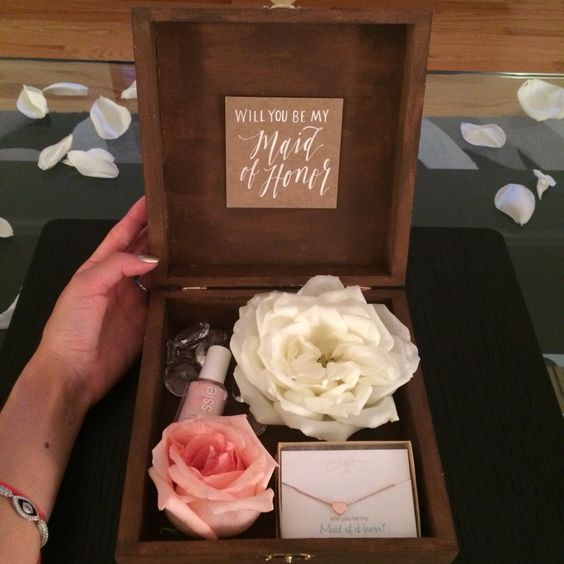 a chic box with fresh blooms, a necklace and pink nail polish to use for the wedding
