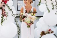 21 a gorgeous wedding arch of white balloons and bold blooms for a modern ceremony