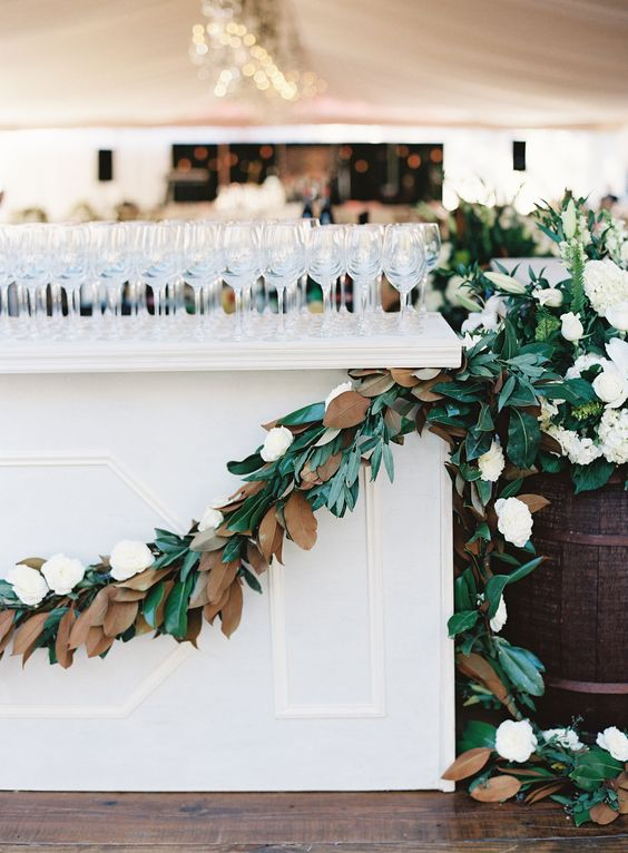 a lush magnolia leaf and white bloom garland on the bar for a chic look