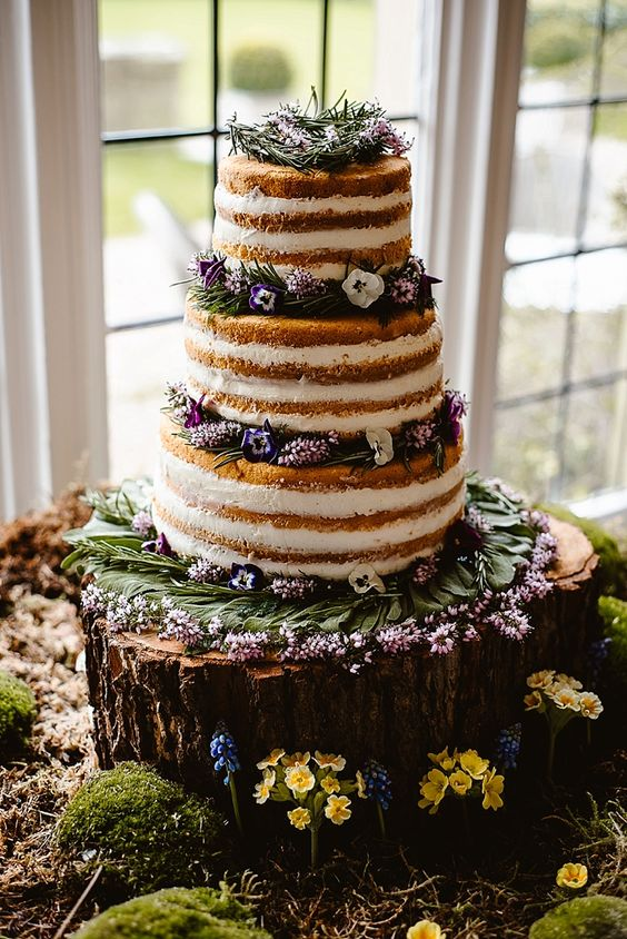 a naked wedding cake with fresh flowers and herbs for a woodland feel
