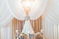 21 a rose gold sequin fabric backdrop plus white draperies, a large rhinestone brooch and a glam chandelier