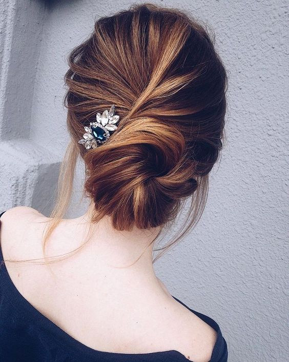 a twisted low bun with some locks down and a pretty small hairpiece