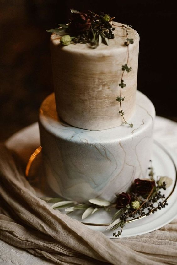 a marble wedding cake with light geen and beige layeres and moody blooms