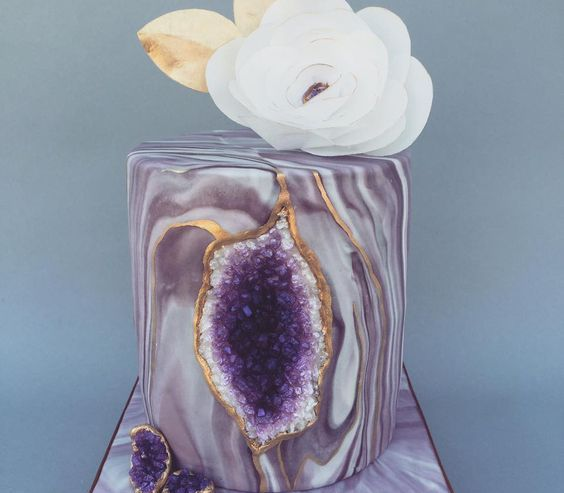 a stunning purple marbleized wedding cake with gold leaf decor and a large bloom on top