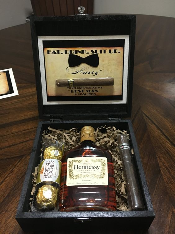 a stylish stained wooden box with chocolate, a cigar and a Hennessy bottle