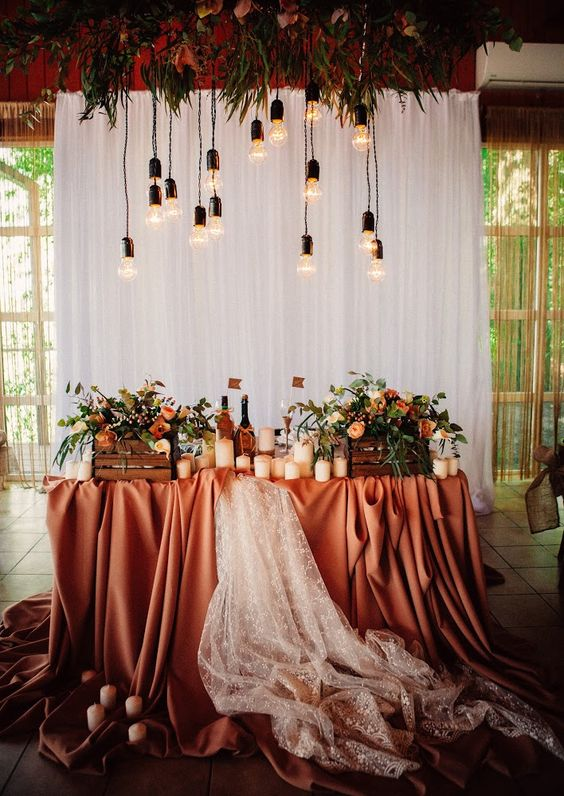 a white curtain backdrop, overhead blooms and bulbs for a fall wedding