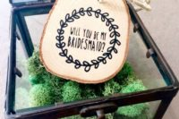 23 a glass box with moss and a wood slice tag is a creative idea that hints on the woodland theme of your wedding