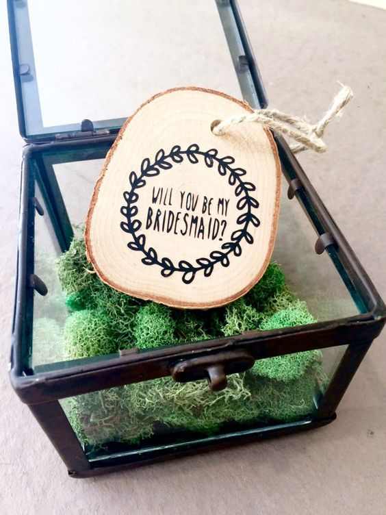 a glass box with moss and a wood slice tag is a creative idea that hints on the woodland theme of your wedding