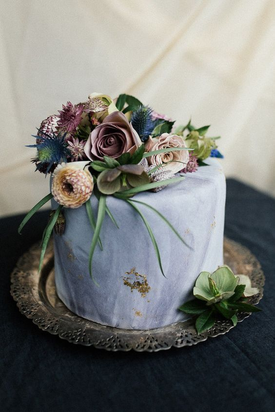 a moody marbleized slate grey wedding cake with moody florals, thistles and air plants