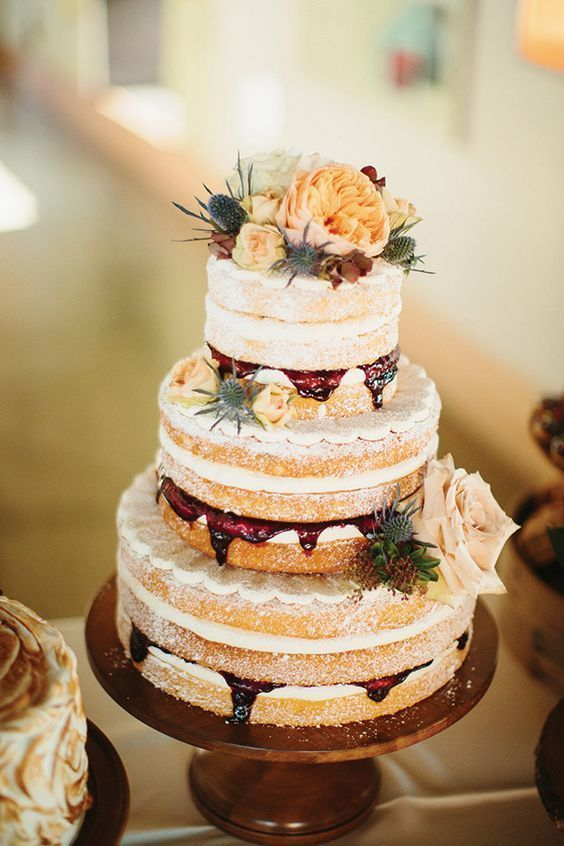 a naked wedding cake with raspberry mousse inside, blush, cream and orange blooms and thistles