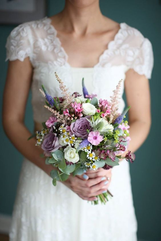 a small ball-like bouquet with pink, mauve, purple, white blooms and greenery for a textural look