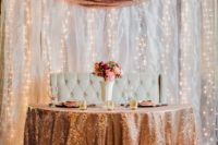 23 a white drapery wall with lots of lights and a sequin runner to match the table decor