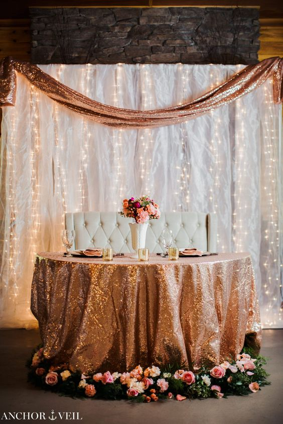 a white drapery wall with lots of lights and a sequin runner to match the table decor