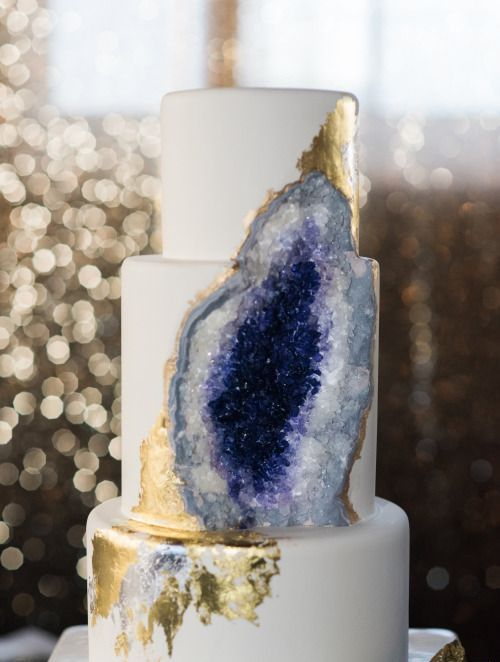 a white wedding cake with amethyst and gold leaf decor looks wow