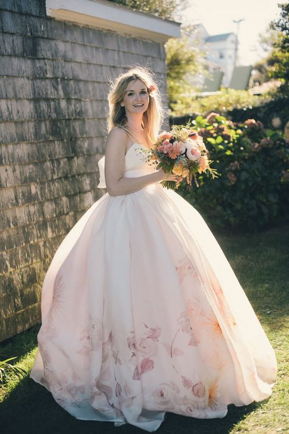 spaghetti strap wedding ballgown with a large bow on the back and floral prints on the skirt