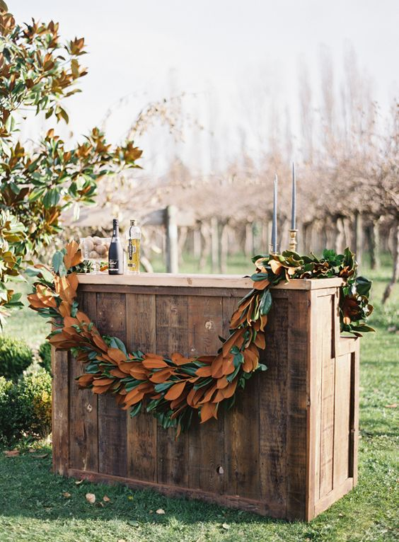 a wedding bar decorated with a lush magnolia leaf garland