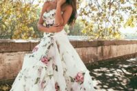 24 strapless ballgown with a draped skirt, a train and soft-colored floral prints on the whole dress