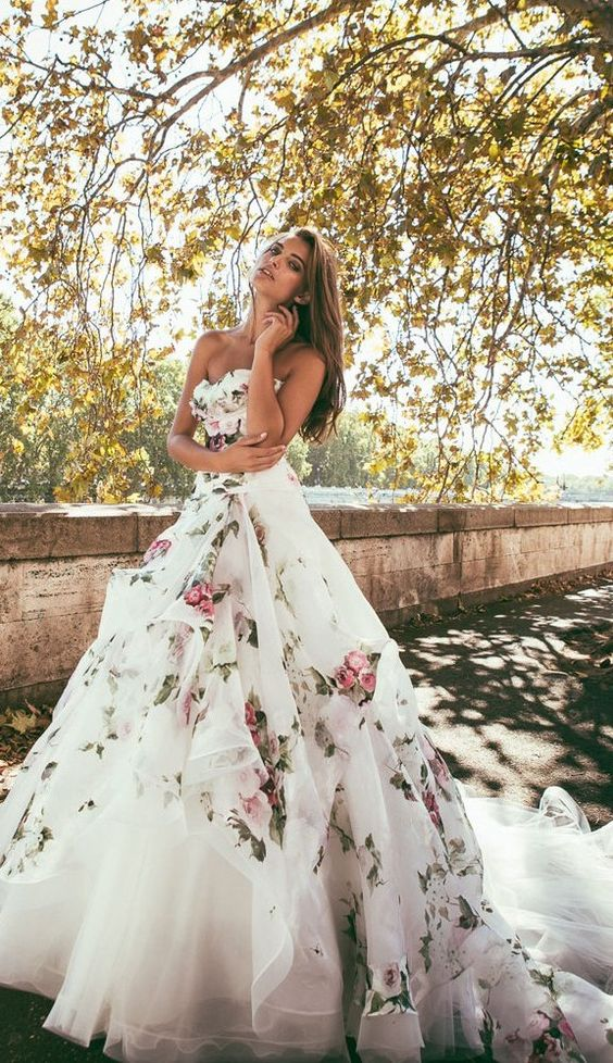 strapless ballgown with a draped skirt, a train and soft-colored floral prints on the whole dress