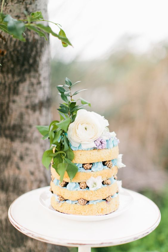 a boho naked wedding cake with blue cream, gilded blackberries, a large blooms and foliage