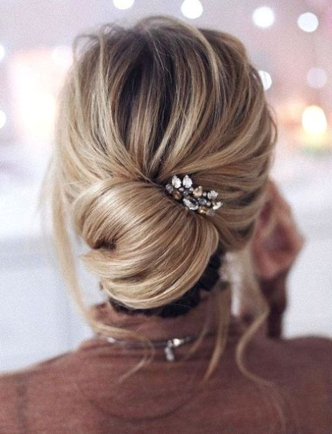 a modern elegant bridesmaid's updo with a low bun, locks down and a rhinestone hairpiece