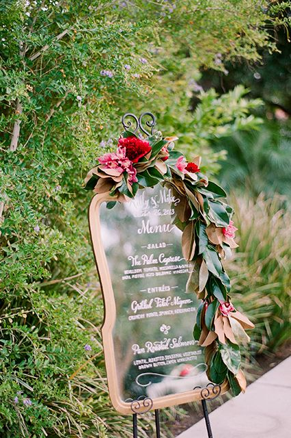 a wedding menu decorated with lush magnolia leaves and bold blooms for a refined feel
