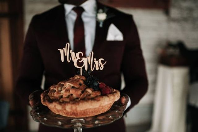 a wedding pie with berries and a cake topper instead of a usual wedding cake