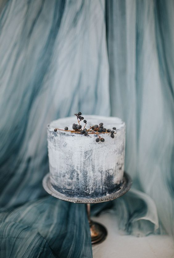 an ombre blue wedding cake with berries on top