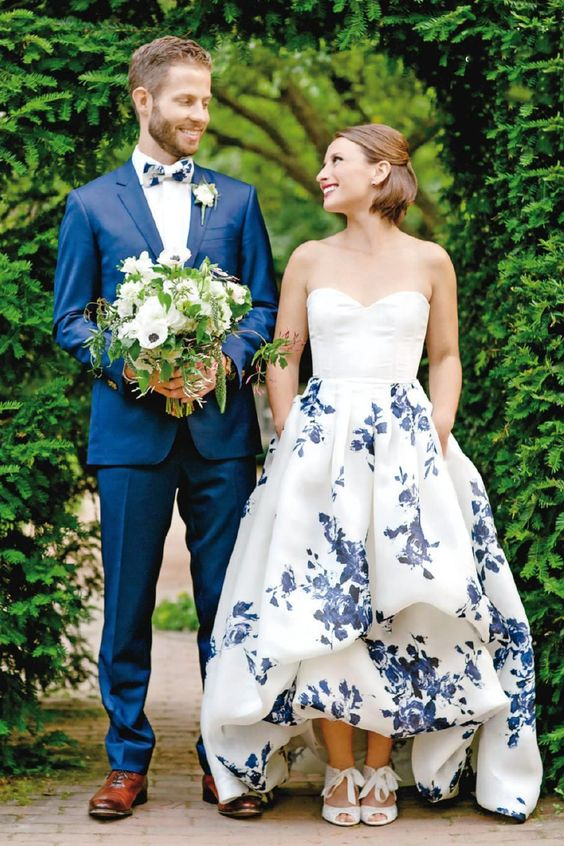 strapless sweetheart neckline wedding dress with a high low skirt and blue floral prints all over the skirt for something blue