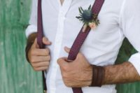 26 tan pants, a white shirt, plum polka dot suspenders and a thistle boutonniere plus leather bracelets
