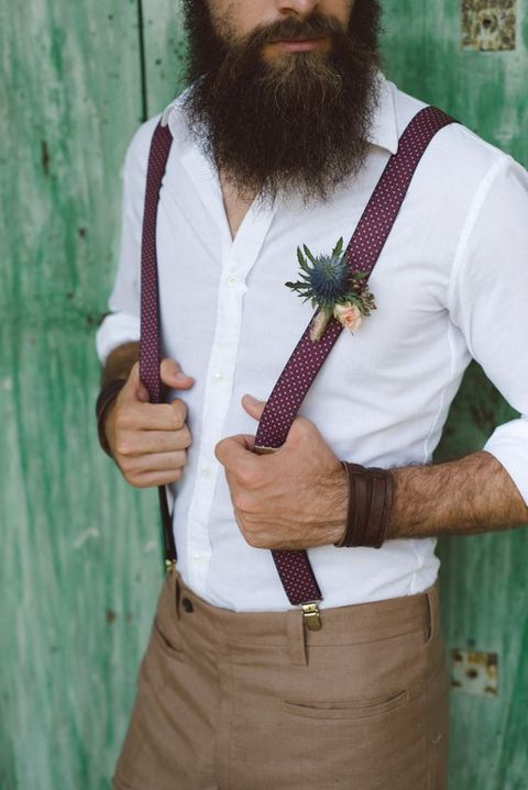 tan pants, a white shirt, plum polka dot suspenders and a thistle boutonniere plus leather bracelets