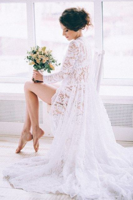 a long white lace bridal robe with long sleeves and a train is stunning and looks beautiful