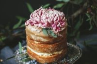 27 a tall yet small naked wedding cake topped with a single large bloom in pink looks elegant