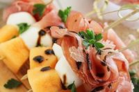28 sweet and salty skewers with prosciutto, melon and creamy mozzarella drizzled with balsamic