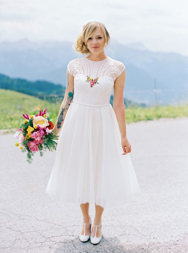The bride was wearing a retro-inspired tea-length wedding dress with colorful floral embroidery, an illusion neckline and T-strap shoes