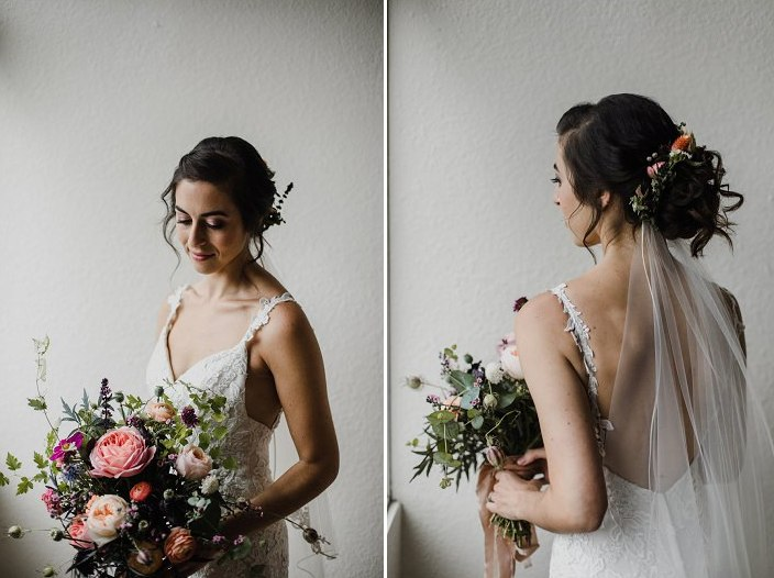 The bride was wearing an elegant wedding dress with lace appliques and an open back, an updo with flowers and stud earrings