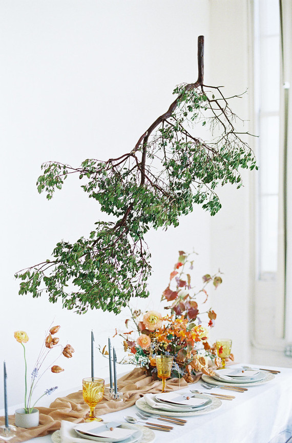 This hanging green branch installation is a gorgeous idea for accenting the tablescape
