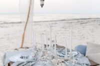 02 a boho beach picnic with a low table placed on the sand, a powder blue table runner and with Moroccan candle holders over it