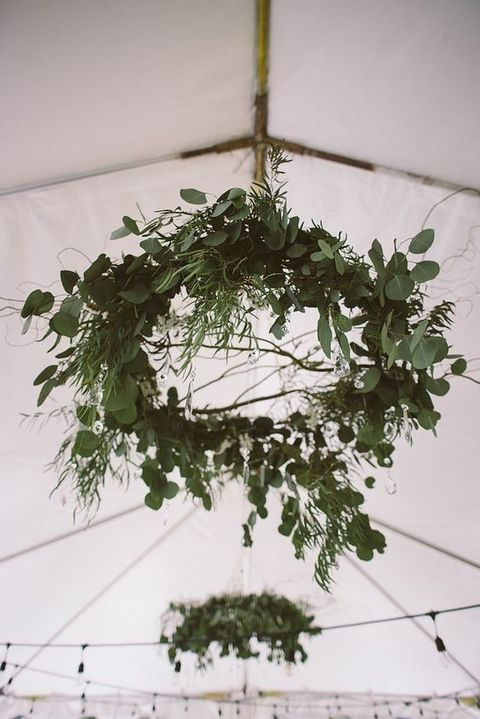 a fresh greenery wreath and chandelier in one for wedding tent decor