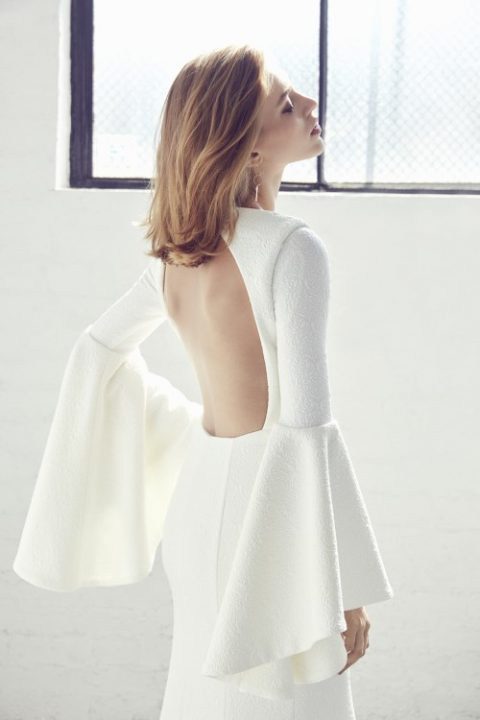 a modern wedding dress with bell sleeves and a cutout back