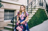 02 a navy floral dress with short sleeves and a full skirt, a pink clutch and nude shoes