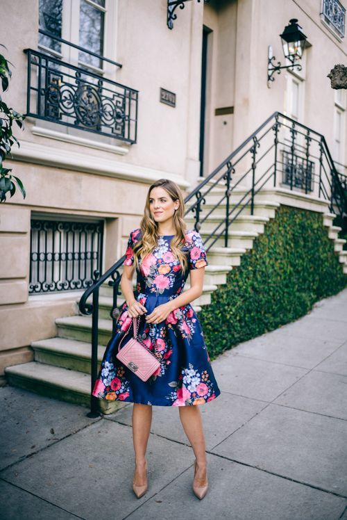 a navy floral dress with short sleeves and a full skirt, a pink clutch and nude shoes