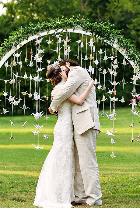 a rounded greenery wedding arch with paper cranes hanging down for a whimsy touch